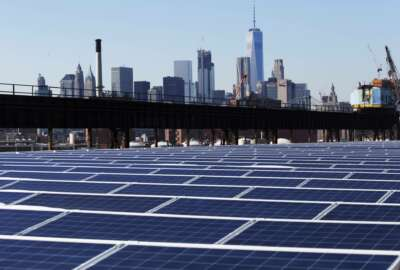 In this Feb. 14, 2017 photo, a rooftop is covered with solar panels at the Brooklyn Navy Yard in New York. The Manhattan skyline is at top. Cheap solar panels imported from China and other countries have led to a boom in the U.S. solar industry, where rooftop and other installations have surged 10-fold since 2011.   (AP Photo/Mark Lennihan)