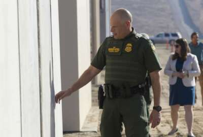 Ronald Vitiello, U.S. Customs and Border Protection's acting deputy commissioner, feels prototypes of a border wall on Thursday, Oct. 26, 2017, in San Diego. Contractors have completed eight prototypes of President Donald Trump's proposed border wall with Mexico, triggering a period of rigorous testing to determine if they can repel sledgehammers, torches, pickaxes and battery-operated tools. (John Gibbins/The San Diego Union-Tribune via AP, Pool)