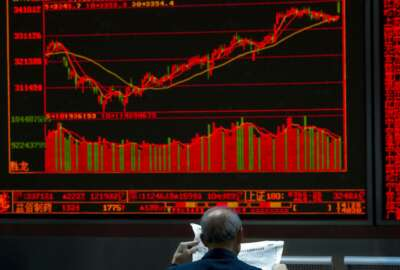 An investor reads a newspaper near a graph showing the Chinese stock market index at a brokerage in Beijing, China, Monday, Oct. 9, 2017. Most Asian markets rose Monday following a strong week on Wall Street as Chinese trading resumed after a holiday. (AP Photo/Ng Han Guan)