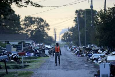 A man walks past debris from homes on his street damaged in flooding from Hurricane Harvey as an oil refinery stands in the background in Port Arthur, Texas, Thursday, Sept. 28, 2017. This historically Democratic county, home to a quarter-million people, is among the low-lying coastal areas that stand the most to lose as the ice caps melt and the seas warm and rise. Yet in November, voters flipped to vote for President Donald Trump, the first Republican they chose in 44 years, who has dismissed the concept of climate change as a hoax perpetrated by China. (AP Photo/David Goldman)