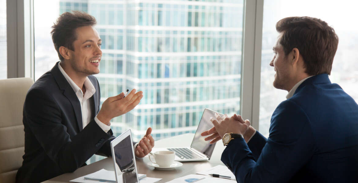 Candid businessman sharing his opinion about work with colleague, telling interesting story when having conversation with partner on coffee-break, making successful negotiation with investor in office