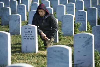 Ken Lai, of Berryville, Va., pauses after placing a wreath at a headstone in Arlington National Cemetery as Wreaths Across America places remembrance wreaths on headstones at the cemetery in Arlington, Va., Saturday, Dec. 16, 2017. (AP Photo/Cliff Owen)