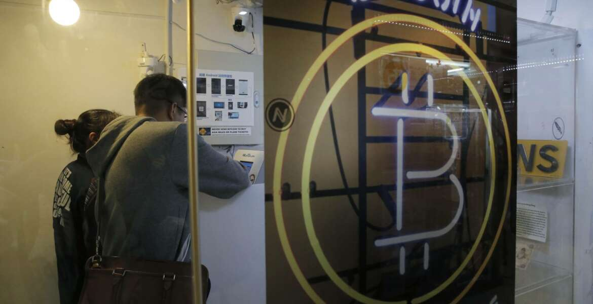 In this Friday, Dec. 8, 2017, photo, people use the Bitcoin ATM in Hong Kong. The launch of a U.S. futures contract for bitcoin on Sunday, Dec. 10, 2017, underscores the virtual currency's increasing mainstream acceptance, including in many parts of Asia, where it already has a wide following among speculators and investors. (AP Photo/Kin Cheung)