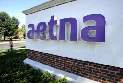 FILE - In this Aug. 19, 2014, file photo, a pedestrian walks by a sign at Aetna headquarters in Hartford, Conn. CVS Health, the second-largest U.S. drugstore chain, is buying Aetna, the third-largest health insurer. The evolution won't happen overnight, but in time, shoppers may find more clinics in CVS stores and more services they can receive through the network of nearly 10,000 locations that the company has built. (AP Photo/Jessica Hill, File)