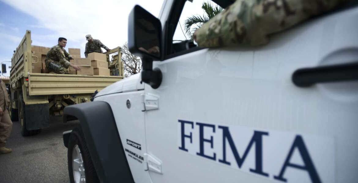FILE - In this Oct. 5, 2017 file photo, Department of Homeland Security personnel deliver supplies to Santa Ana community residents in the aftermath of Hurricane Maria in Guayama, Puerto Rico. The U.S. Federal Emergency Management Agency (FEMA) is rejecting on Monday, Dec. 18, 2017  a report by Refugees International criticizing local and federal hurricane response in Puerto Rico. (AP Photo/Carlos Giusti, File)