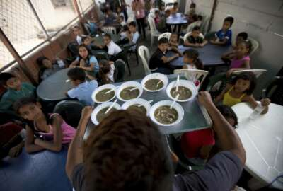 In this Dec. 12, 2017 photo, children watch their free meal arrive to be served at a soup kitchen sponsored by the opposition in Caracas, Venezuela. Venezuela's opposition leaders are reinventing themselves, meeting their country's growing number of poor in their own neighborhoods. (AP Photo/Fernando Llano)