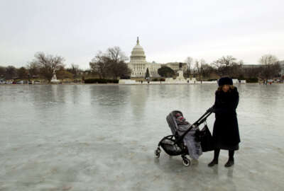 A visitor push her stroller on the frozen reflecting pool, outside of the U.S. Capitol, Wednesday, Jan. 3, 2018, in Washington. Forecasters warned that conditions could worsen, especially in the Northeast. ( AP Photo/Jose Luis Magana)