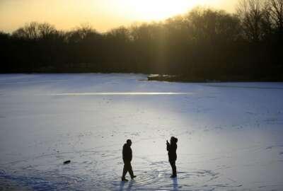 A couple takes photographs on a frozen pond at Franklin Delano Roosevelt Park in Philadelphia, Wednesday, Jan. 3, 2018. (AP Photo/Matt Rourke)