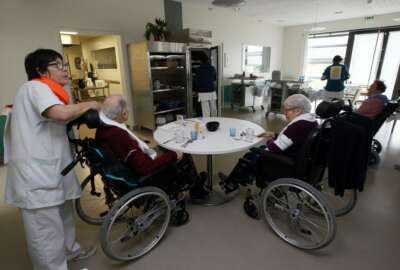 A care worker takes care to residents of the Maharin nursing home of Anglet, southwestern France, Tuesday, Jan.30, 2018. French care workers are protesting at nursing homes around the country in anger over staff shortages and cost cuts. Unions say workers are under increasing pressure to cut corners on feeding, cleaning and hygiene care for elderly residents. (AP Photo/Bob Edme)