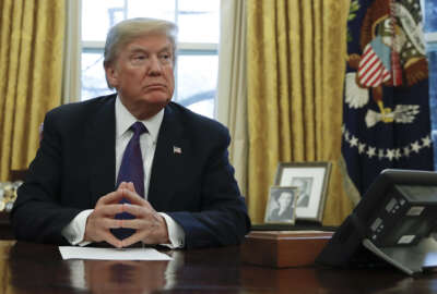 President Donald Trump prepares to sign Section 201actions in the Oval Office of the White House in Washington, Tuesday, Jan. 23, 2018. Trump says he is imposing new tariffs to
