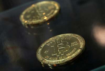 """FILE- In this Dec. 8, 2017, file photo, coins are displayed next to a Bitcoin ATM in Hong Kong. The IRS says that cryptocurrency transactions are taxable by law. That means people who made money (or lost it) on Bitcoin trades, """"mined"""" Ethereum or even bought a cup of coffee with digital currency face potential tax implications. Failure to report it could mean potential audits, fines and penalties. (AP Photo/Kin Cheung, File)"""
