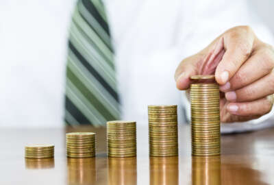 Businessman hand holding coin dollar on money coin stack arranged as a graph on wooden table, concept of money growth and saving money