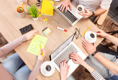 Top view of creative team using laptops and drinking coffee. Men and women are sitting at desk in office