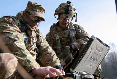 Sgt. 1st Class Joseph Rombold (left), an observer coach at Hohenfels Training Area, Germany, shows Spc. William Ritter (right), a military policeman with 287th Military Police Company, 97th Military Police Battalion, 89th Military Police Brigade, Fort Riley, Kansas, how to properly set up the system to operate the RQ-11 Raven, a small unmanned aerial system (sUAS), during Allied Spirit VIII at Hohenfels, Germany, Jan. 26, 2018. Roughly 4,100 troops from 10 nations are participating in Allied Spirit VIII, a multinational training exercise designed to test participants' readiness and capabilities.
