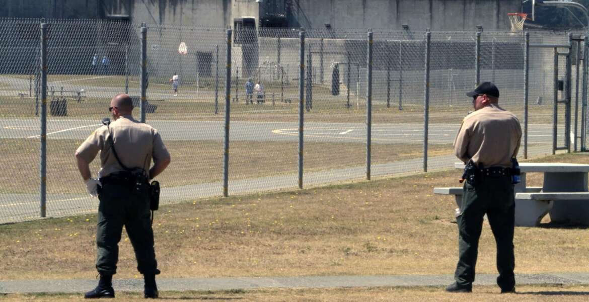 FILE - In this Aug. 17, 2011 file photo, correctional officers keep watch on inmates in the recreation yard at Pelican Bay State Prison near Crescent City, Calif. Gov. Jerry Brown will appeal a judge's ruling that California must consider earlier parole for potentially thousands of sex offenders, such as those convicted of raping an unconscious person. Corrections department spokeswoman Vicky Waters said the administration will fight the order made final Monday, March 5, 2018, by Sacramento County Superior Court Judge Allen Sumner. (AP Photo/Rich Pedroncelli, File)