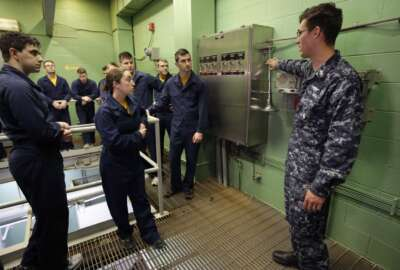 In this April 26, 2017 photo U.S. Navy Petty Officer First Class Clinton Benson, of Stanton, Mich., right, speaks to a class, including U.S. Navy Ensign Megan Stevenson, of Raymond, Maine, center left, at the Naval Submarine School, in Groton, Conn. The Navy began bringing female officers on board submarines in 2010, followed by enlisted female sailors five years later. Their retention rates are on par with those of men, according to records obtained by The Associated Press. (AP Photo/Steven Senne)