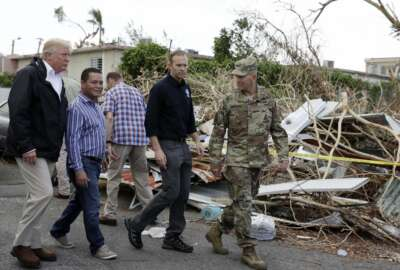 FILE - In this Oct. 3, 2017 file photo, President Donald Trump walks with FEMA administrator Brock Long, second from right, and Lt. Gen. Jeff Buchanan, right, during a tour of an area affected by Hurricane Maria in Guaynabo, Puerto Rico. Puerto Rican officials say the Trump administration is neglecting the territory because it doesn't have votes in Congress or presidential elections. The Trump administration has blamed Puerto Rico for creating delays in the disbursement process, but has not been more specific. (AP Photo/Evan Vucci, File)