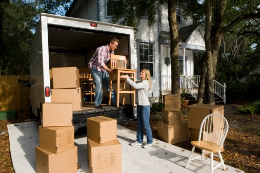 Mid adult couple unloading chairs and cardboard boxes from the moving van