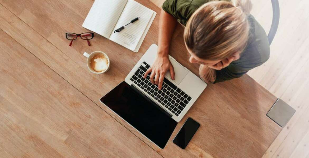 Top view of woman using laptop while sitting at cafe table with laptop, mobile phone, diary, coffee cup and glasses. Female surfing internet at coffee shop.
