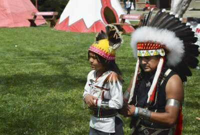 Deshava Apachee, 38, of Dulce, N.M. prepares his son, Noah to dance at the Gathering of Nations, one of the world's largest gatherings of indigenous people, in Albuquerque, N.M. on Friday, April 27, 2018. The Native American event is a powwow, a pan-American Indian celebration featuring song, dance and prayer. They are held in stadiums, rural community centers or high school gyms and offer an opportunity for American Indians from different tribal nations with diverse histories to come together to reaffirm their shared experiences and reunite with friends. (AP Photo/ Russell Contreras)