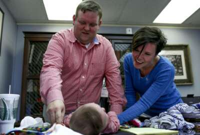 In this March 23, 2018 photo, Philip Ellison and his wife, Katherine Ellison, change their son Patton's clothing at the end of the work day at Philip Ellison's firm Outside Legal Counsel in Hemlock, Mich. If you were born in Michigan in July 1984 or later, you may be among more than five million people whose blood is being held by the state of Michigan, some of which may be used in medical research. A federal lawsuit, filed by Saginaw County Attorney Ellison on behalf of a group of Michigan parents, argues that the practice is unconstitutional and there are no protections in place to stop police or others from accessing the information that can be derived from stored blood samples. (Henry Taylor/The Flint Journal-MLive.com via AP)