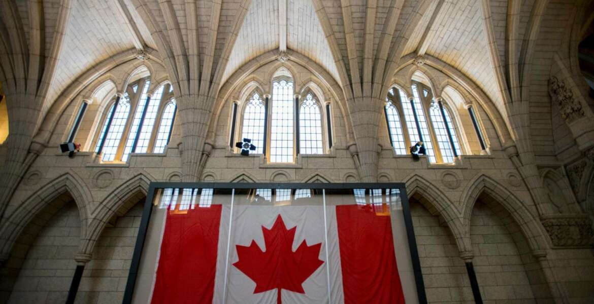 FILE - In this Feb. 14, 2015, file photo, the Maple Leaf flag believed to be the one to be first raised above the Peace Tower on Feb. 15, 1965, following resolution and creation of a distinctive Canadian flag, is seen in a display case in the Hall of Honour on Parliament Hill in Ottawa, Ontario. An online story falsely claims Canadians now can be jailed simply for using an incorrect gender pronoun. The article posted to The Daily Signal website said a law enacted in 2017 would lead to hate crime charges against people who use an incorrect pronoun to describe a transgender person. (Justin Tang/The Canadian Press via AP, File)