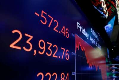 """FILE- In this April 6, 2018, file photo, a screen above the trading floor of the New York Stock Exchange shows the closing number for the Dow Jones industrial average. While the stock market was busy heaving up and down in recent months, some funds were offering a steadier, slightly less-nauseating ride. """"Low-volatility"""" funds cater to skittish investors who have less tolerance for turbulent markets. (AP Photo/Richard Drew, File)"""