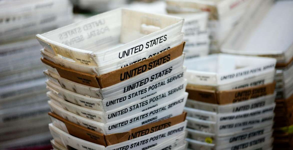 FILE- In this Dec. 14, 2017, file photo, boxes for sorted mail are stacked at the main post office in Omaha, Neb. A task force will study the U.S. Postal Service under an executive order from President Donald Trump, who has spent weeks criticizing online retailer Amazon and accused it of not paying enough in shipping costs. (AP Photo/Nati Harnik, File)