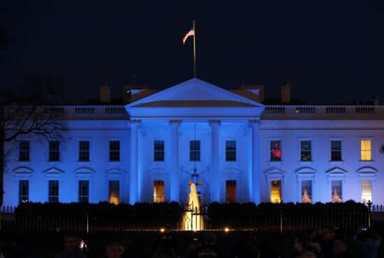 FILE - In this April 2, 2017, file photo, the White House is lit with blue lights in honor of World Autism Awareness Day in Washington. Top U.S. tech executives and researchers are gathering at a White House summit, Thursday, May 10, 2018, to press Trump administration officials on investing in artificial intelligence and crafting policies they hope will strengthen the economy without displacing jobs. (AP Photo/Alex Brandon, File)