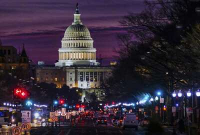 FILE - In Dec. 14, 2016 file photo, early morning traffic rolls down Pennsylvania Avenue toward the U.S. Capitol as daybreaks in Washington.   The federal government swung to a surplus of $214.3 billion in April, 2018 primarily reflecting the revenue from that month's annual tax filing deadline. The Treasury Department reports that last month's surplus increased 17.4 percent from a year ago. (AP Photo/J. David Ake, File)