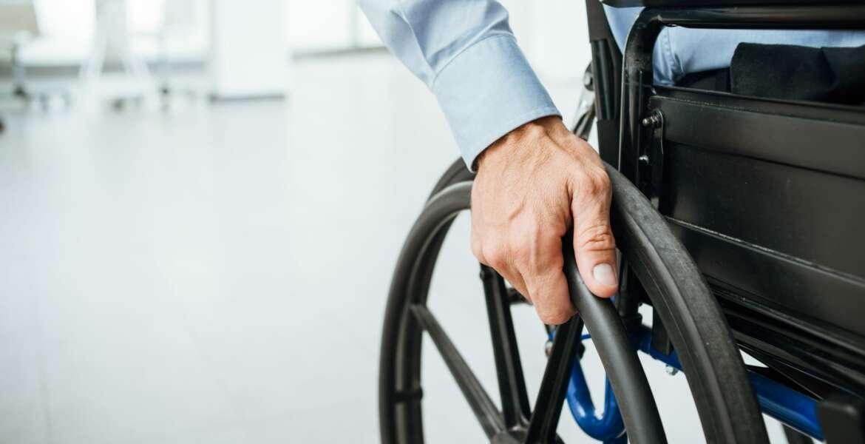 Businessman in wheelchair, hand on wheel close up, office interior on background