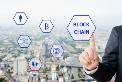 Businessman hand touching block chain icon over blur city background, cryptocurrency, bitcoin concept