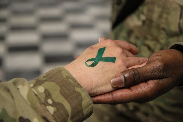 U.S. Army Sgt. 1st Class Tyrone Lawrence, right, places a temporary teal ribbon tattoo on a Soldier's hand at the Koele dining facility at Bagram Airfield in Parwan province, Afghanistan, April 2, 2014. The teal ribbon was the symbol of sexual assault survivors and awareness. (DoD photo by Staff Sgt. Kelly Simon, U.S. Army/Released)