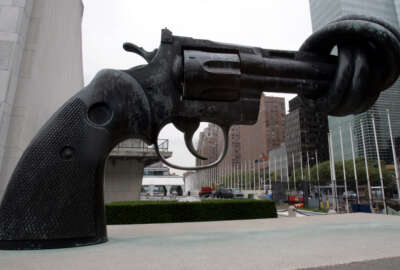 The sculpture of a hand gun with a knotted barrel is seen in front of the United Nations building in New York, Tuesday, Aug. 16, 2005. (AP Photo/Frank Franklin II)