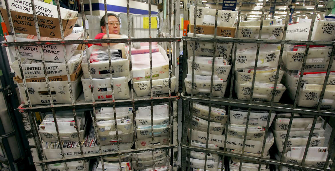 Mail handler Rolanda Ramos sorts through mail at the United States Postal Service Processing and Distribution Center in San Francisco, Wednesday, Dec. 21, 2005. Today is the busiest delivery day of the year for the postal service, according to Jim Larkin of the USPS, who estimates approximately 15 million pieces of mail being shipped. (AP Photo/Jeff Chiu)