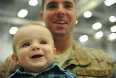 Aiden Robillard smiles in the arms of his father, Staff Sgt. Tim Robillard, Jan. 12, 2014, at Hurlburt Field, Fla. Robillard was met by his wife and son after returning home from deployment. Robillard is a 801st Special Operations Aircraft Maintenance Squadron electric and environmental systems maintainer. (U.S. Air Force photo by Staff Sgt. John Bainter/Released)