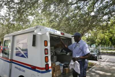 In this June 14, 2018, file photo, Elston Bradshaw, a mail carrier for the United States Postal Service closes a mail truck door after delivering mail to an apartment complex in Aventura, Fla. Amazon's Prime shipping program set the pace for shoppers' expectations, and the nation's largest online player continues to look for new ways to keep up with shoppers' demands. (AP Photo/Brynn Anderson, File)