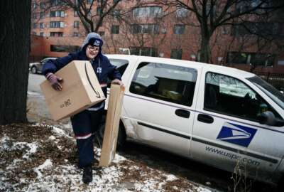 FILE- In this Dec. 24, 2017, file photo, United States Postal Service worker Missie Kittok, who has been a letter carrier for 15 months, helps deliver some packages in time for Christmas in Minneapolis, Amazon's Prime shipping program set the pace for shoppers' expectations, and the nation's largest online player continues to look for new ways to keep up with shoppers' demands. That's forcing other companies to radically think of new initiatives to get products to shoppers' doors faster. (Richard Tsong-Taatarii/Star Tribune via AP, File)