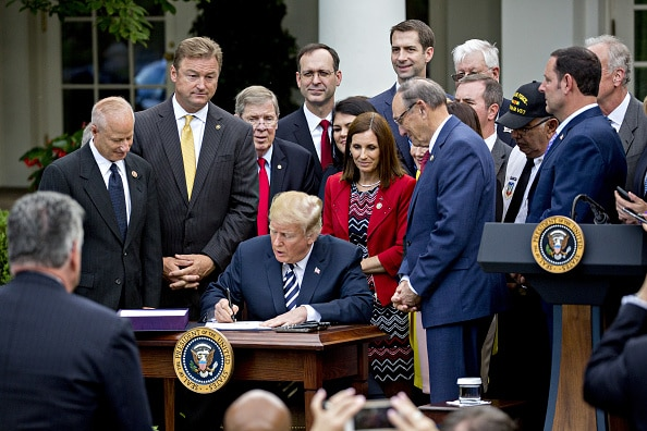 U.S. President Donald Trump signs S. 2372, the VA Mission Act of 2018, during a ceremony in the Rose Garden of the White House in Washington, D.C., U.S., on Wednesday, June 6, 2018. The bill is targeted at expanding veterans access to private-sector health care. Photographer: Andrew Harrer/Bloomberg via Getty Images