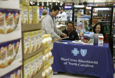 FILE - In this file photo taken Nov. 22, 2014, Blue Bridge Benefits LLC agent Patricia Sarabia, right, and Adolfo Briceno, left, with Spanish Speaking LLC, help a potential customer with Blue Cross Blue Shield at a kiosk promoting Obama Care at Compare Foods in Winston-Salem, N.C. A new poll finds that more than half of Hispanic adults have encountered a communication barrier in the health care system. (AP Photo/Gerry Broome, file)