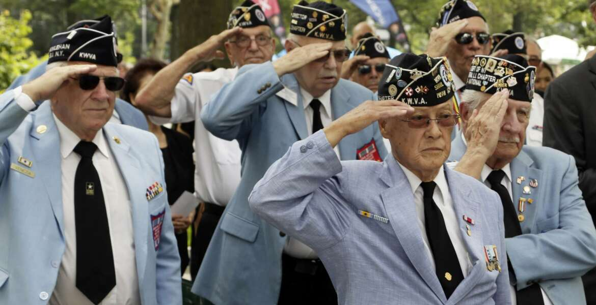 Korean War Veterans salute as the honor guard presents the American flag at the Korean War memorial at Battery Park in New York, Friday, July 27, 2018. Korean War veterans have something extra to celebrate as they mark the 65th anniversary of the armistice that ended combat. (AP Photo/Stephen Groves)