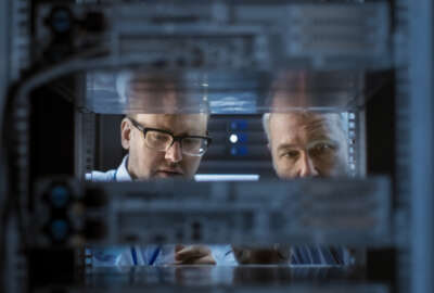 Two Server Engineers Install Hardware in Server Rack. They Work in Big Modern Data Center.