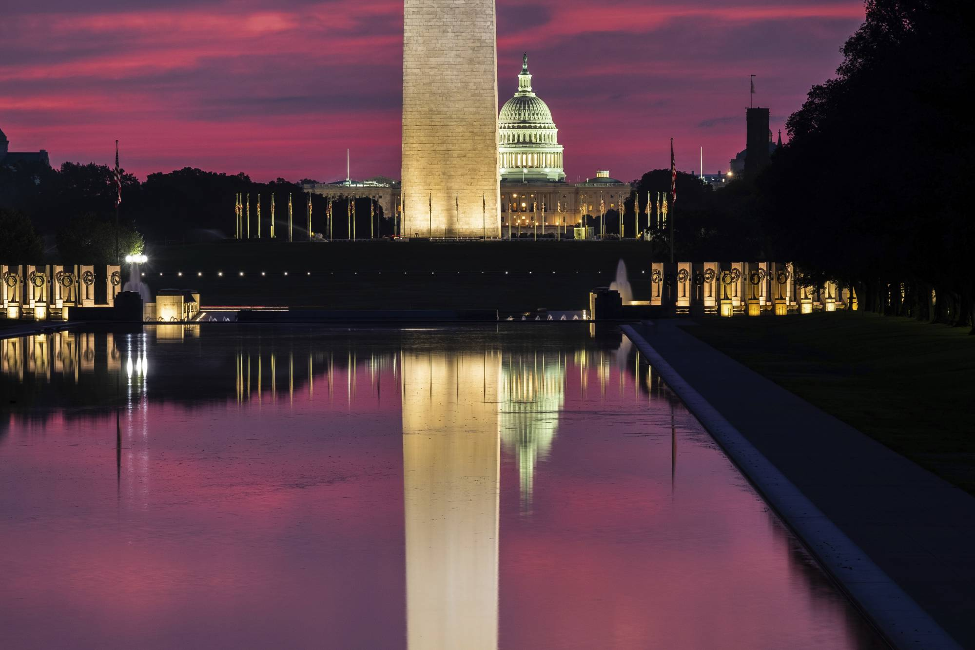 The U.S. Capitol and the base of the Washington Monument are mirrored in the reflecting pool on the National Mall at sunrise in Washington, Saturday, Aug. 25, 2018. (AP Photo/J. David Ake)