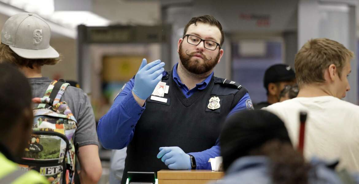 A TSA agent calls passengers forward for screening at Sea-Tac International Airport Friday evening, Aug. 10, 2018, in SeaTac, Wash. An airline mechanic stole an Alaska Airlines plane without any passengers and took off from Sea-Tac International Airport in Washington state on Friday night before crashing near Ketron Island, officials said. (AP Photo/Elaine Thompson)