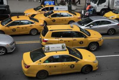 In this Wednesday, Aug. 1, 2018 photo, yellow cabs make their way across 42nd Street outside Grand Central Terminal in New York. Responding to tales of financial woe, New York City lawmakers are considering a proposal to try and stabilize the city's iconic taxi industry by putting a temporary cap on the number of drivers working for companies like Uber and Lyft. The restrictions come after a year in which many drivers for-hire in the city have complained that the explosion in the popularity of ride-hailing services has upended regulations intended to limit competition and ensure that every driver made enough money to survive. (AP Photo/Mary Altaffer)