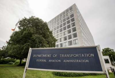FILE - In this June 19, 2015 file photo, Department of Transportation Federal Aviation Administration building is seen in Washington. The FAA would be required to set new minimum requirements for seats on airplanes under legislation to be considered in the House this week. The regulation of seat width and legroom is part of a five-year extension of federal aviation programs agreed to early Saturday, Sept. 22, 2018, by Republican and Democratic leaders of the House and Senate committees that oversee the nation's air travel. (AP Photo/Andrew Harnik, File)