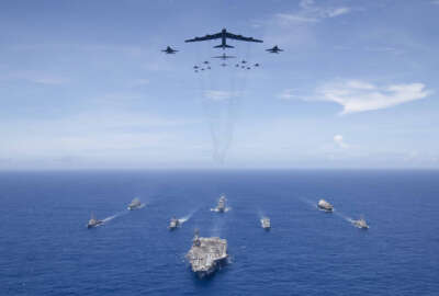 PHILIPPINE SEA (Sept. 17, 2018) The aircraft carrier USS Ronald Reagan (CVN 76) leads a formation of Carrier Strike Group (CSG) 5 ships as U.S. Air Force B-52 Stratofortress aircraft and U.S. Navy F/A-18 Hornets pass overhead for a photo exercise during Valiant Shield 2018. The biennial, U.S. only, field-training exercise focuses on integration of joint training among the U.S. Navy, Air Force and Marine Corps.
