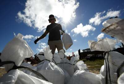 A Virginia Beach, Va., resident moves a sandbag before loading it in his truck, Wednesday, Sept. 12, 2018, in Virginia Beach, Va., as Hurricane Florence moves towards the eastern shore. The National Hurricane Center's projected track had Florence hovering off the southern North Carolina coast from Thursday night until landfall Saturday morning or so, about a day later than previously expected. The track also shifted somewhat south and west, throwing Georgia into peril as Florence moves inland. (AP Photo/Alex Brandon)