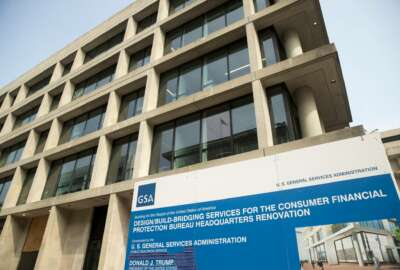 FILE- In this Aug. 27, 2018, file photo a sign stands at the construction site for the Consumer Financial Protection Bureau's new headquarters in Washington. The nation's financial watchdog has opened a formal investigation into writings and comments by Eric Blankenstein, a Republican appointee overseeing the agency's anti-discrimination efforts, which he alleged that most hate crimes were fake and argued that using racial epithets did not mean a person was racist. (AP Photo/Andrew Harnik, File)