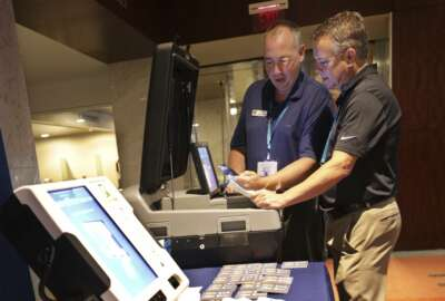 In this July 14, 2018, photo, Election Systems & Software (ES&S), CEO Tom Burt, right, looks at some of the company's election equipment in the vendor display area at a National Association of Secretaries of State convention in Philadelphia. Experts say top election vendors have long skimped on security in favor of convenience and use proprietary systems, making it more difficult to detect election meddling. (AP Photo/Mel Evans)